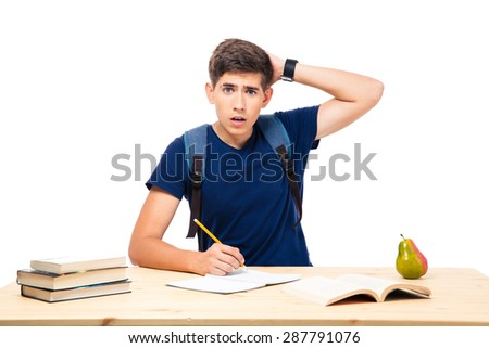 Young male student sitting at the table and writing in notebook isolated on a white background. Looking at camera - stock photo