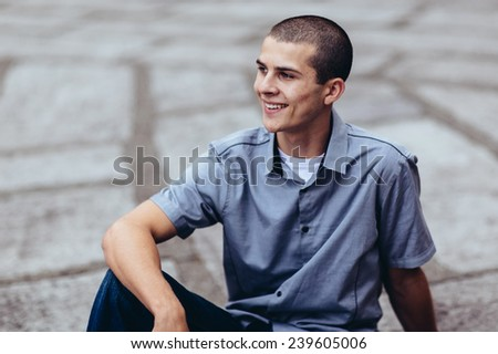young male student, sitting on ground, arm on leg, smiling away from camera - stock photo