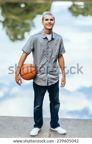young male student, standing in front of fountain water reflection, smiling, holding basketball - stock photo