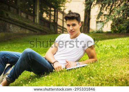Young Male Student Studying his Lessons while Lying on Grass in City Park, Smiling at Camera