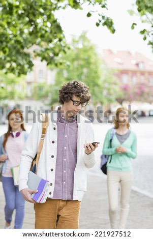 Young male student using cell phone with friends in background on street - stock photo