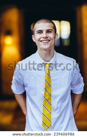 young male student, with tie, smiling, arms behind back - stock photo