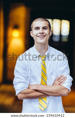 young male student, with tie, smiling, arms folded - stock photo