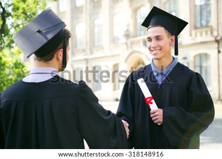Young male students dressed in black graduation gown. Campus as a background. Boys holding diplomas and shaking hands - stock photo