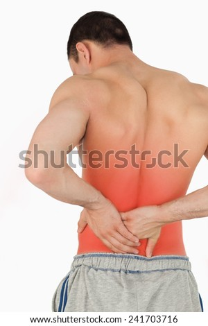 Young male suffering from back pain against a white background