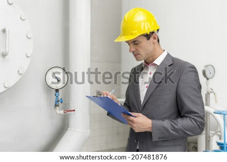 Young male supervisor inspecting pipeline in industry - stock photo