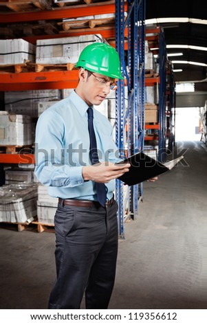 Young male supervisor reading book at warehouse - stock photo