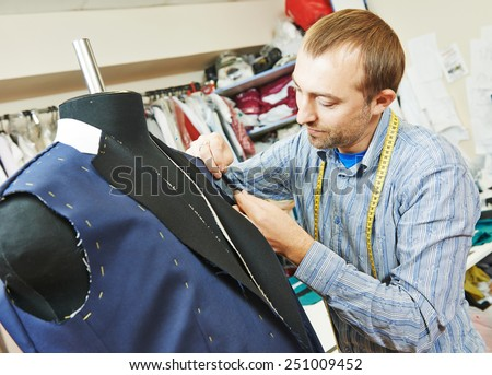 young male tailor portrait in workshop - stock photo