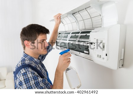 Young Male Technician Cleaning Air Conditioner At Home