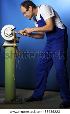 Young male technician in blue overall working on grinding bench in workshop, blue background. - stock photo
