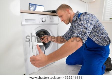 Young Male Technician Making Washing Machine In Kitchen - stock photo