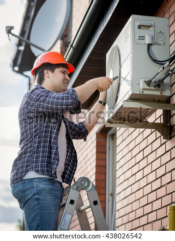 Young male technician repairing outdoor air conditioning system - stock photo