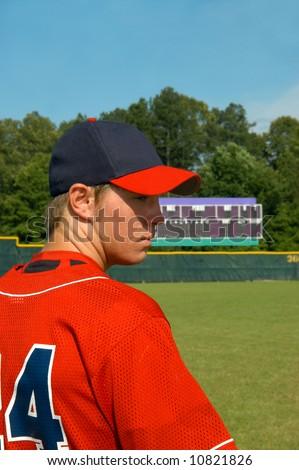 Young male teen baseball player looks sideways.  Scoreboard is in background. - stock photo