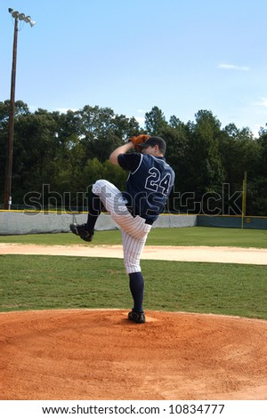 Young male teen winds up for the pitch.  Navy and white uniform.  Blue skies and baseball field. - stock photo