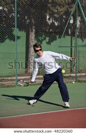 Young male tennis player in action - stock photo