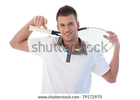 Young male tennis player taking a break, smiling, holding tennis racket.? - stock photo