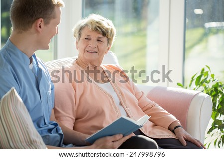 Young male therapist spending time together with his older ward - stock photo