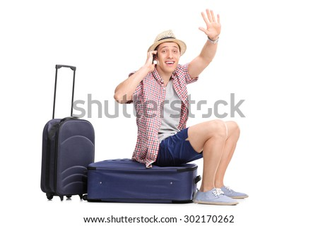 Young male tourist talking on cell phone and waving with his hand seated on his baggage isolated on white background - stock photo
