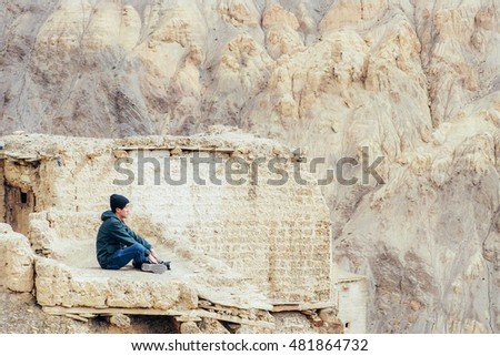 Young male traveler sitting on the sand cliff, thinking about something in Leh, Ladakh, India.