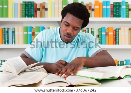Young male university student studying at desk in library - stock photo