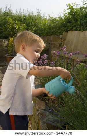 Young male watering garden. Toy watering can used to sprinkle herb garden. - stock photo