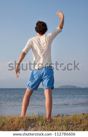 Young male waving hands at sea side - stock photo