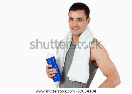 Young male with a bottle after workout against a white background - stock photo