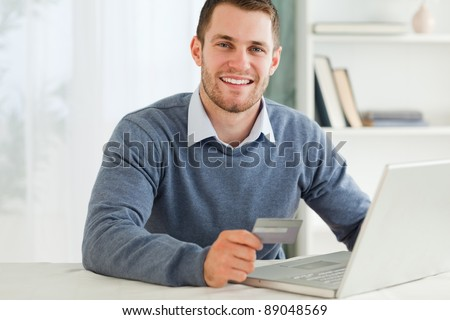 Young male with credit card at his laptop - stock photo