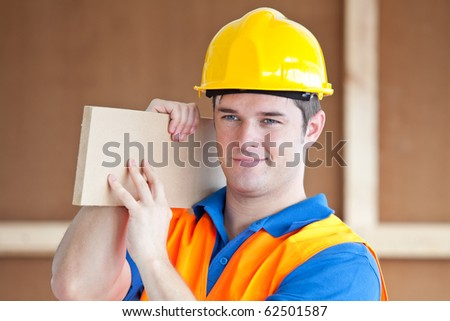 Young male worker carrying a wooden board at work