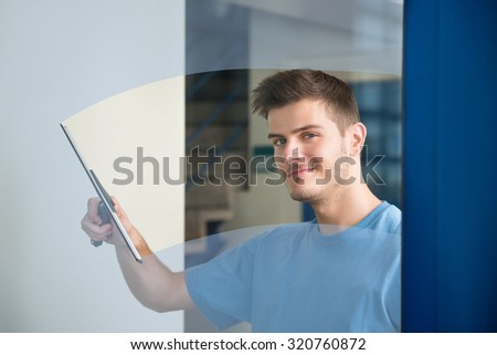 Young Male Worker Cleaning Glass With Squeegee - stock photo