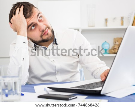 Young male worker having problem in project in office
