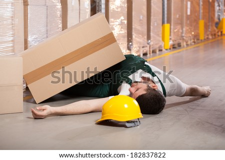 Young male worker lying on the floor in warehouse - stock photo