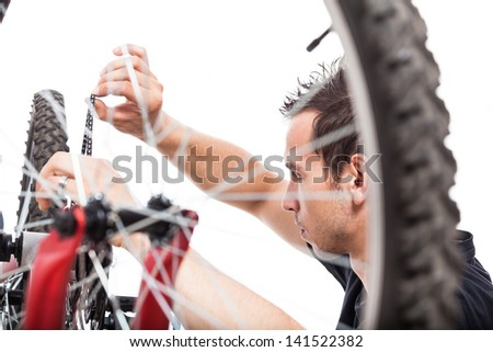 Young man adjusting bike chain and repairing bicycle, isolated on white background - stock photo