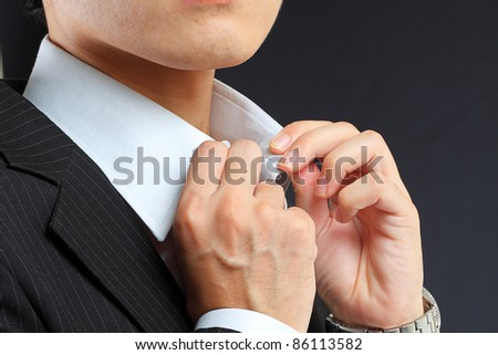 young man adjusting his suit on a black background - stock photo