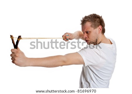Young man aiming a slingshot poses in the studio on a white background - stock photo