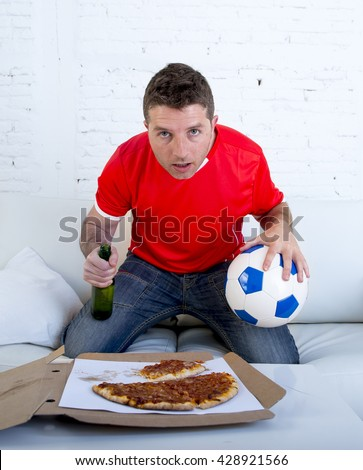 young man alone holding ball and beer bottle in stress wearing team jersey watching football game on television at home living room sofa couch with pizza box excited and in disbelief face expression - stock photo
