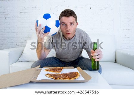 young man alone holding ball and beer bottle watching football game on television sitting at home living room sofa couch with pizza box enjoying the match looking nervous and excited - stock photo