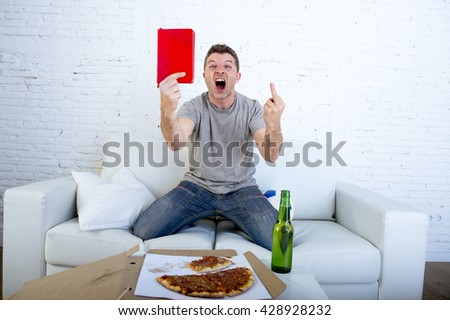 young man alone holding notepad showing it as referee red card in angry face giving the finger in stress watching football game on television at home couch with pizza box and beer bottle screaming - stock photo