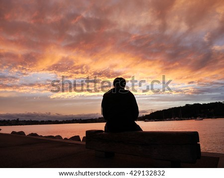 Young man alone is looking at the sunrise