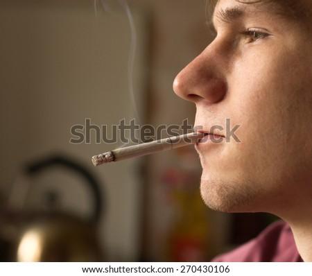 young man alone smokes cigarettes - stock photo
