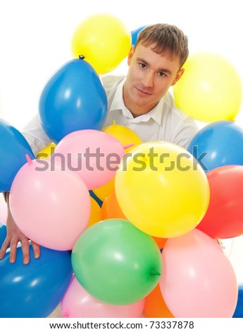Young man among colorful balloons