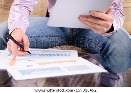 Young man analyzing charts with digital tablet pc - stock photo