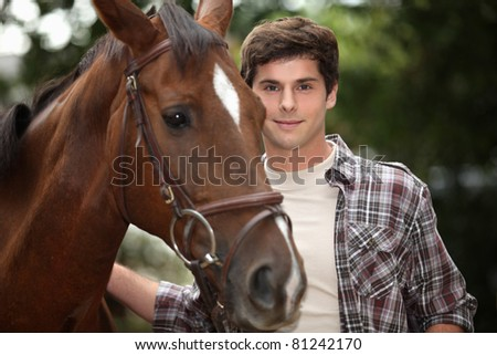 young man and a horse in the forest - stock photo