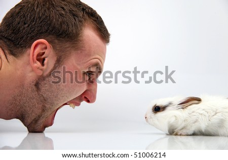 Young man and a rabbit on white background - stock photo