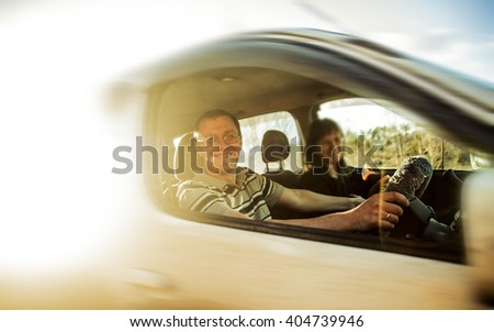 Young man and adult woman sitting in a car. Sunny spring or summer day. Smiling face.