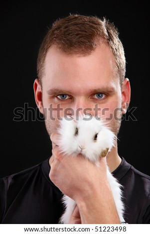 Young man and domestic rabbit on black background in the studio, close-up shot - stock photo