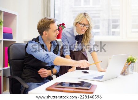 Young man and female colleagues working together in the office - stock photo