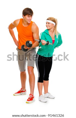 Young man and fitness girl lifting a dumbbell isolated on white - stock photo