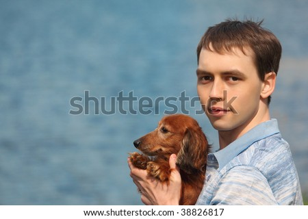 Young man and his adorable dachshund closeup against water - stock photo