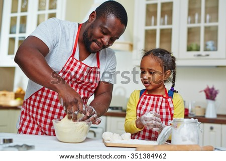 Young man and his daughter making pastry in the kitchen - stock photo